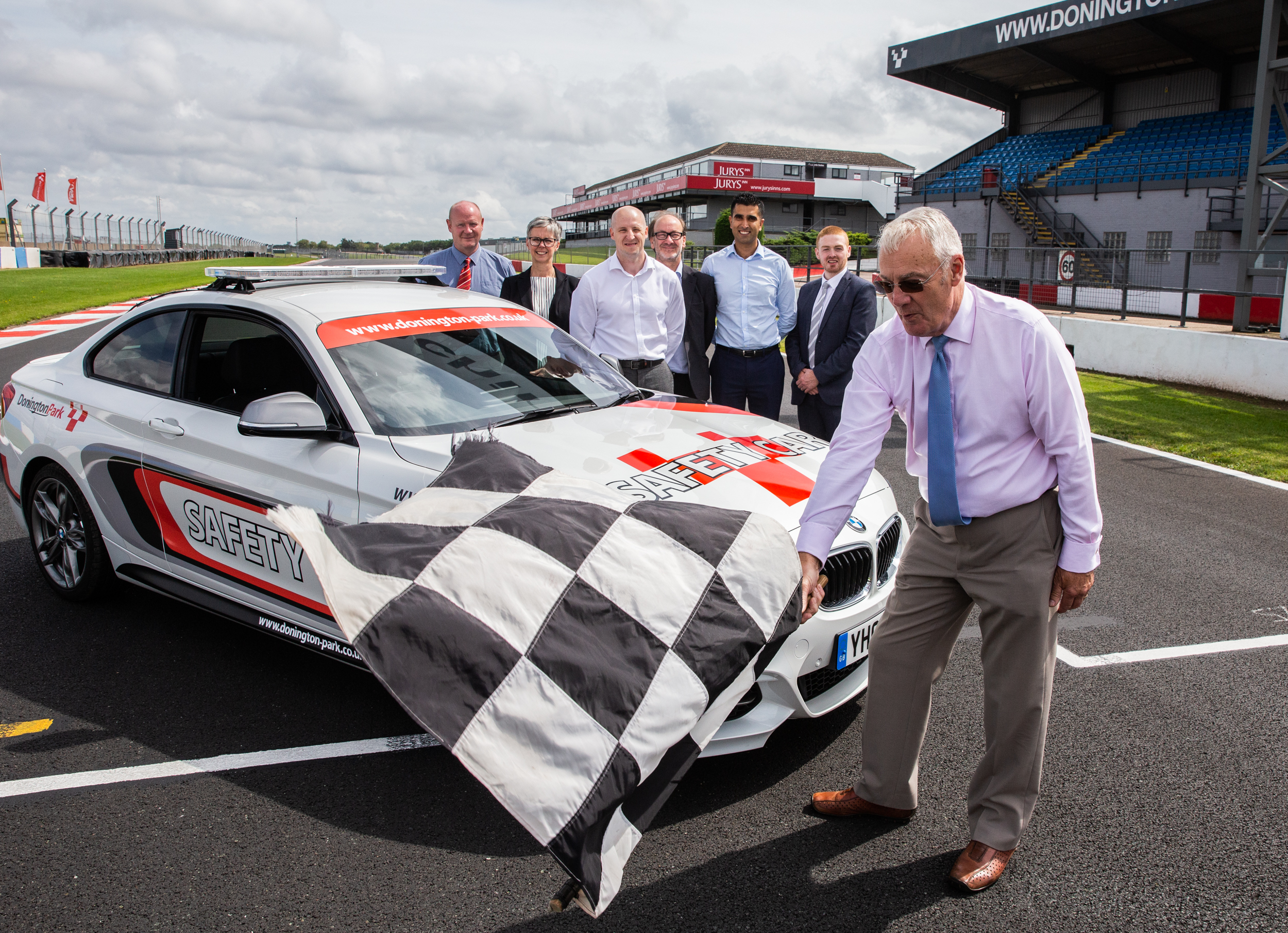 safety car with members of BT, Openreach and the DCMS standing on racetrack and one man holding chequered flag in the wind